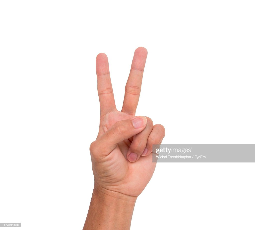 Cropped Image Of Hand Showing Victory Sign Against White Background : Stock-Foto