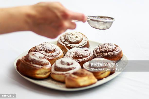 Cropped Image Of Hand Sprinkling Powdered Sugar Over Pastries In Plate