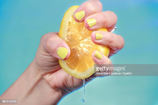 cropped image of hand squeezing fruit against blue sky - zitrone stock-fotos und bilder