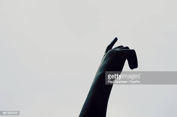 Cropped Image Of Hand Statue At Pere Lachaise Cemetery Against Clear Sky
