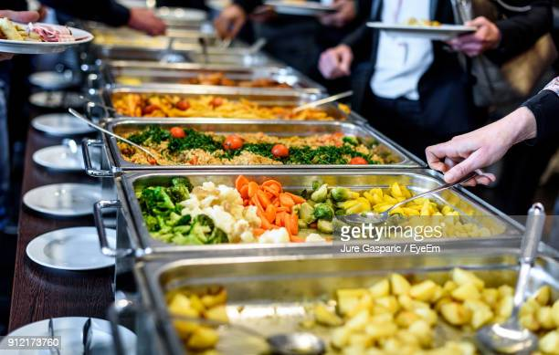 cropped image of hand taking food - buffet stock pictures, royalty-free photos & images