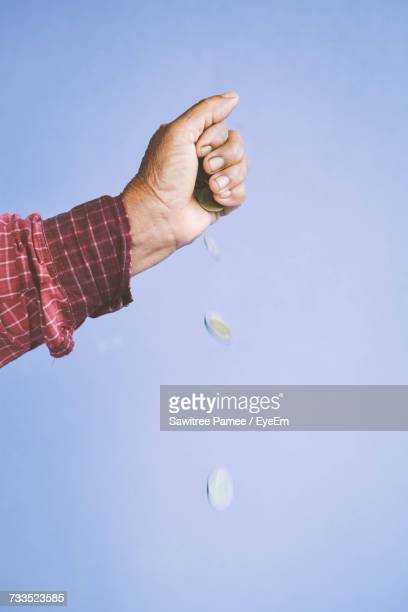 Cropped Image Of Hand Throwing Coins Against Purple Background