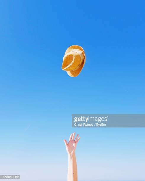 cropped image of hand throwing hat against clear blue sky - blue hat stock pictures, royalty-free photos & images