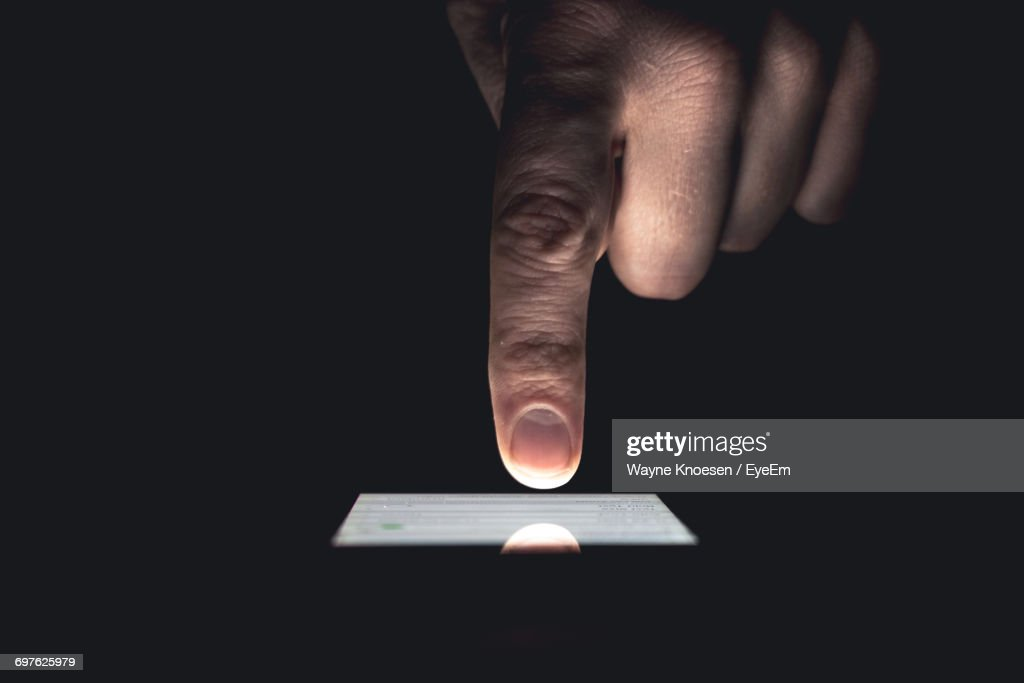 Cropped Image Of Hand Touching Mobile Screen Over Black Background : Stock-Foto