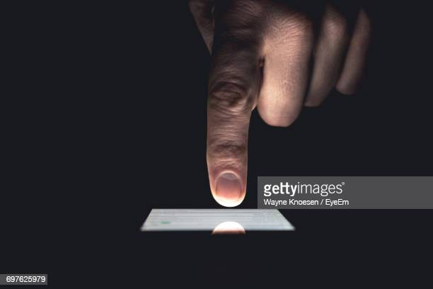 cropped image of hand touching mobile screen over black background - nicht erkennbare person stock-fotos und bilder