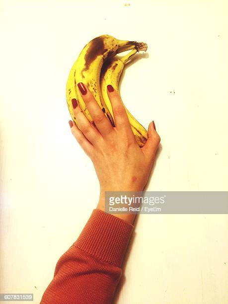 cropped image of hand touching ripe bananas on table - danielle reid stock pictures, royalty-free photos & images