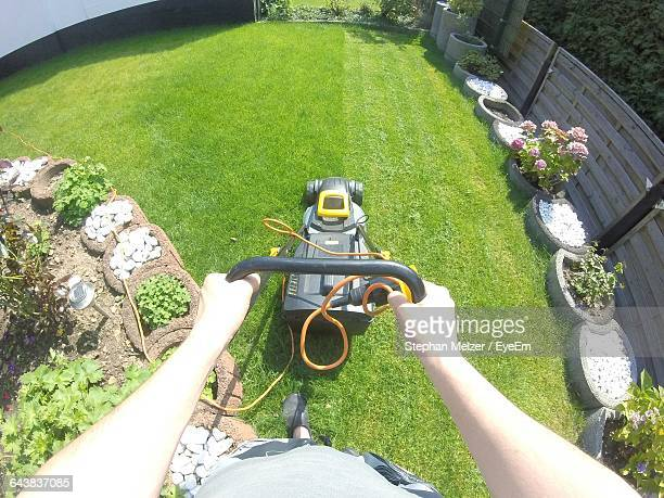 Cropped Image Of Hand Using Lawn Mower At Yard