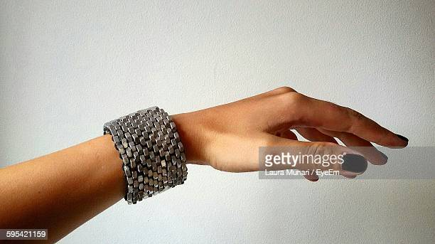 cropped image of hand wearing bracelet against wall - brazalete pulsera fotografías e imágenes de stock