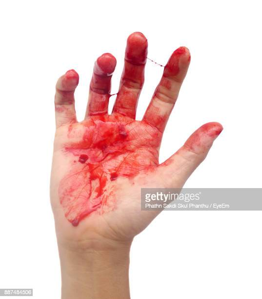 cropped image of hand with blood over white background - bloody hand stock photos and pictures