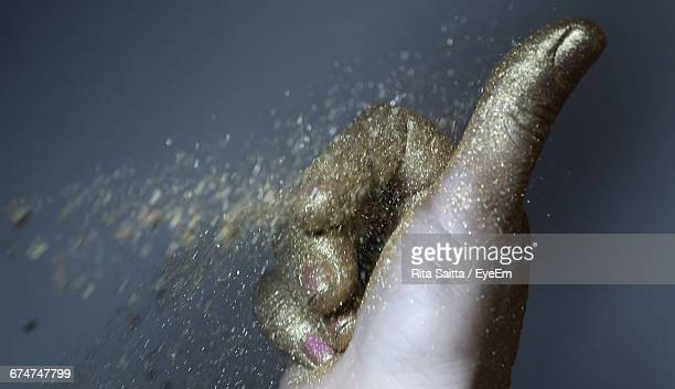 Cropped Image Of Hand With Gold Glittering Powder Paint Against Gray Background