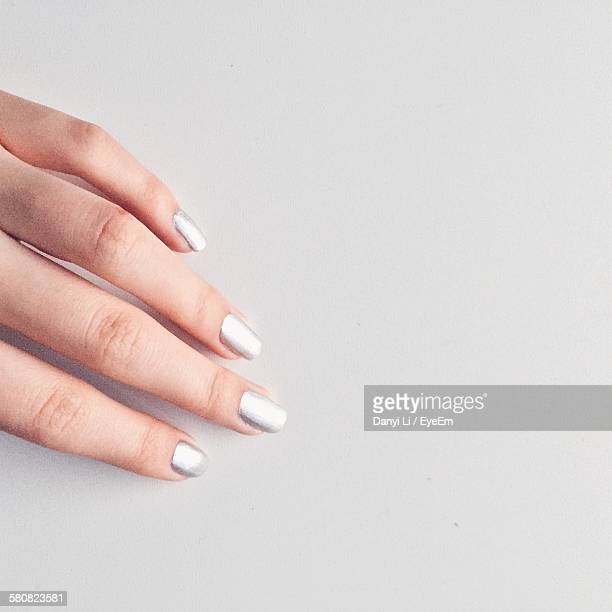 Cropped Image Of Hand With Nail Polish Against White Background