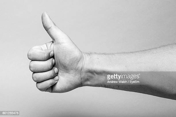 Cropped Image Of Hand With Thumb Up Against Wall