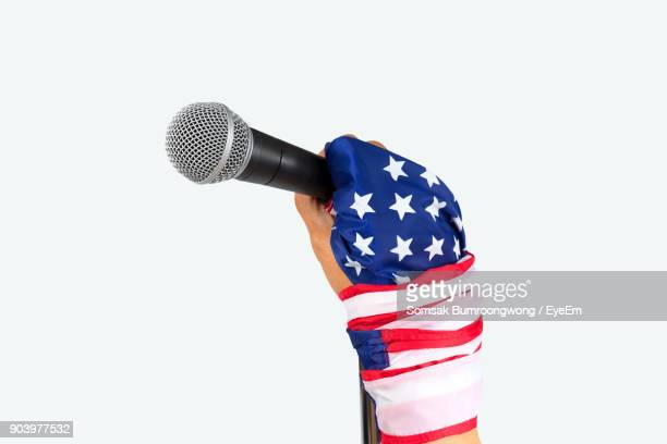Cropped Image Of Hand Wrapped In American Flag Holding Microphone Against White Background