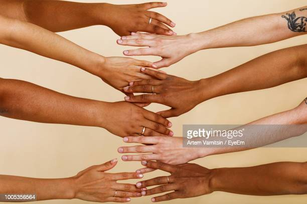 cropped image of hands against beige background - human arm stock pictures, royalty-free photos & images