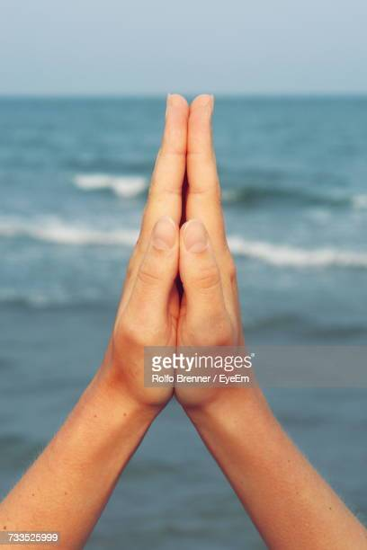 Cropped Image Of Hands Clasped Against Sea