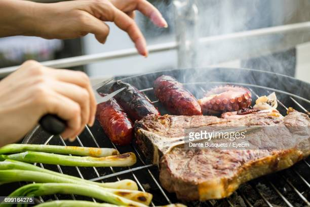 Cropped Image Of Hands Cooking Meat And Octopus On Barbecue Grill