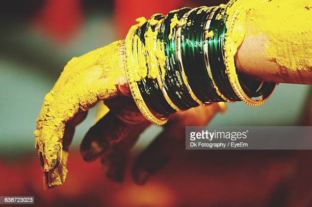 Cropped Image Of Hands Covered With Turmeric Paste During Wedding Ceremony