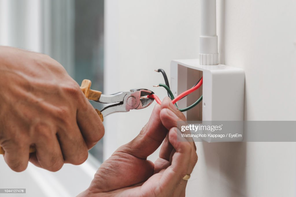 Cropped Image Of Hands Cutting Cable : Stock Photo