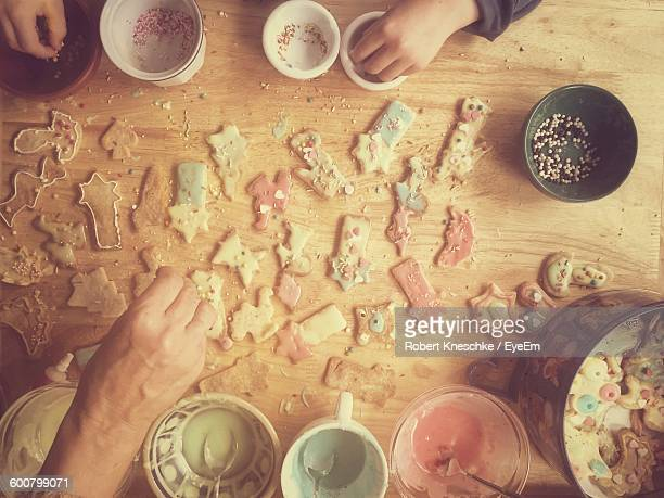 Cropped Image Of Hands Decorating Gingerbread Cookies