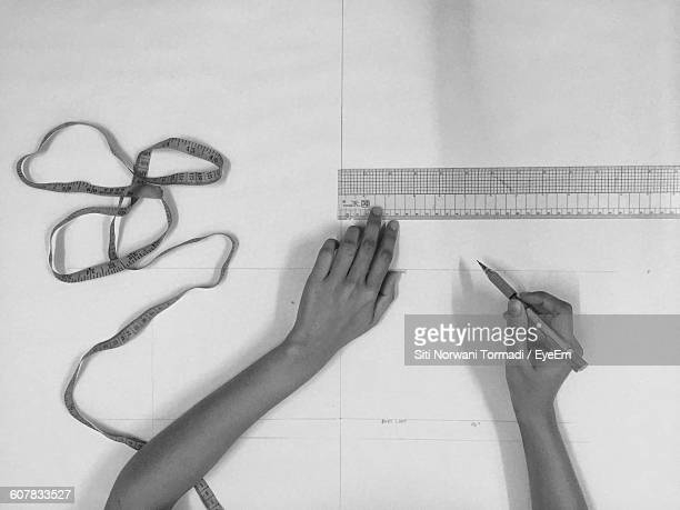 Cropped Image Of Hands Drawing Lines On Paper