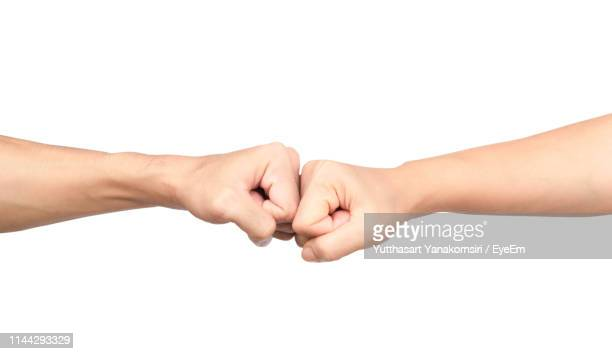 cropped image of hands fist bumping against white background - fist bump stock pictures, royalty-free photos & images