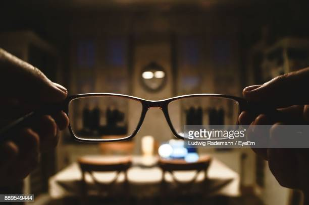 cropped image of hands holding eyeglasses - rademann stock pictures, royalty-free photos & images