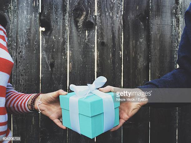 cropped image of hands holding gift box against wooden fence - exchanging stock pictures, royalty-free photos & images