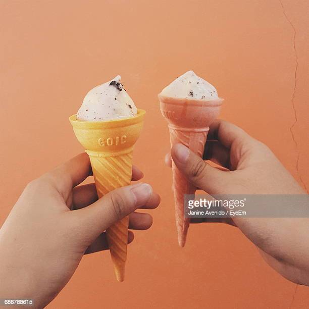 Cropped Image Of Hands Holding Ice Creams Against Wall