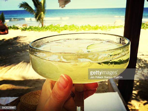 cropped image of hands holding margarita in glass - margarita beach stock photos and pictures