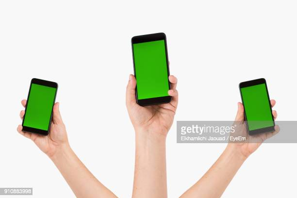 Cropped Image Of Hands Holding Mobile Phone Over White Background
