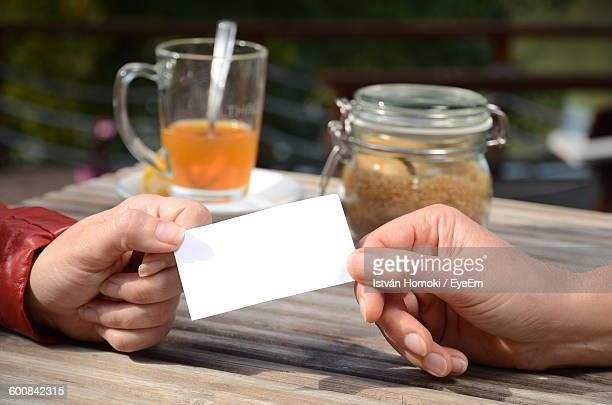 Cropped Image Of Hands Holding Paper At Table