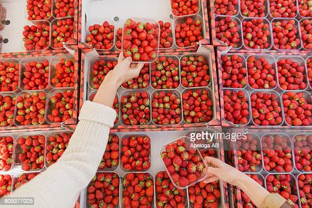 Cropped image of hands holding strawberries on display at stall