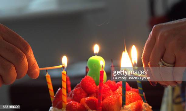 Cropped Image Of Hands Lighting Birthday Candles