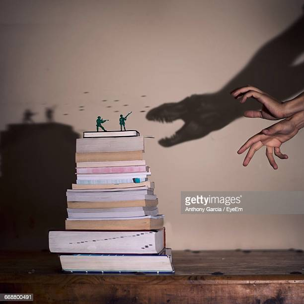 cropped image of hands making dinosaur shadow attacking on soldier figurines on books - santa clarita stock pictures, royalty-free photos & images