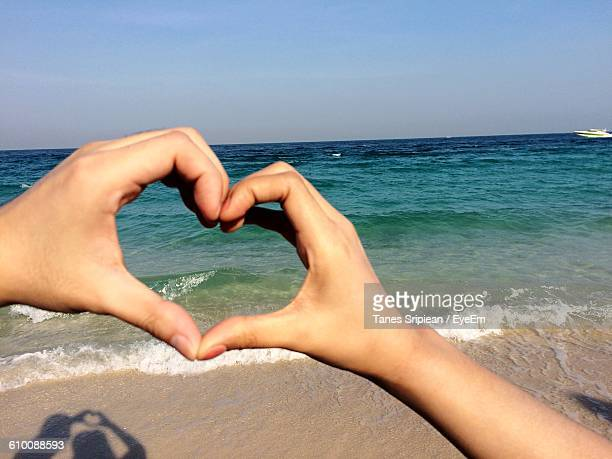 Cropped Image Of Hands Making Heart Shape Against Sea