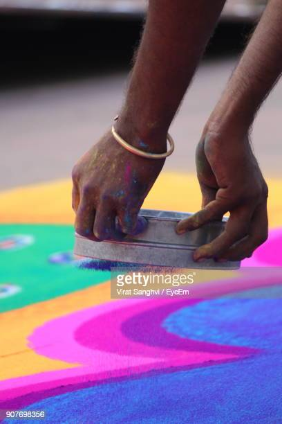 Cropped Image Of Hands Making Rangoli