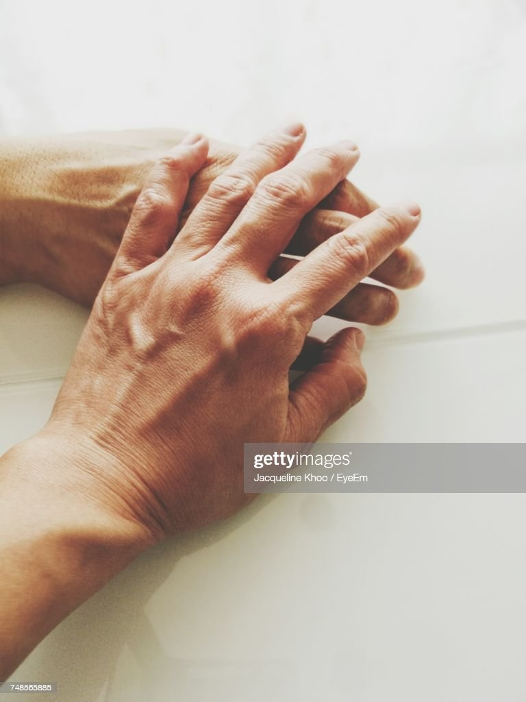 Cropped Image Of Hands On Table : Stock-Foto