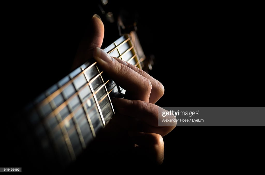 Cropped Image Of Hands Playing Guitar Against Black Background : Stock Photo