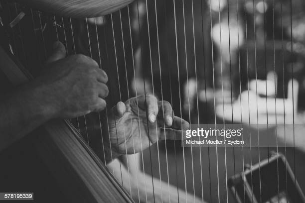 Cropped Image Of Hands Playing Harp