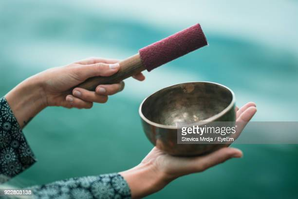 cropped image of hands playing singing bowl - gong stock photos and pictures