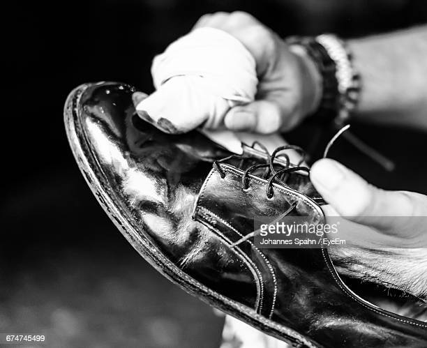 Cropped Image Of Hands Polishing Shoe