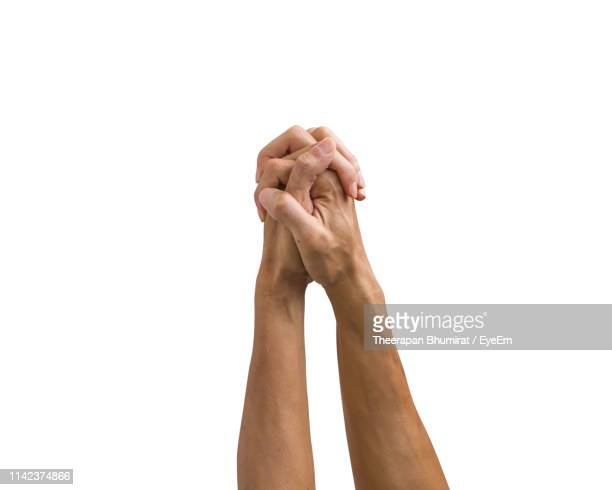 cropped image of hands praying against white background - mani incrociate foto e immagini stock
