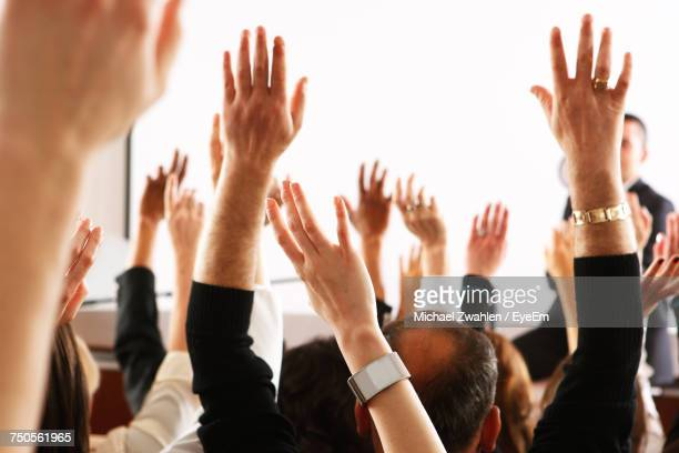 Cropped Image Of Hands Raised At Seminar