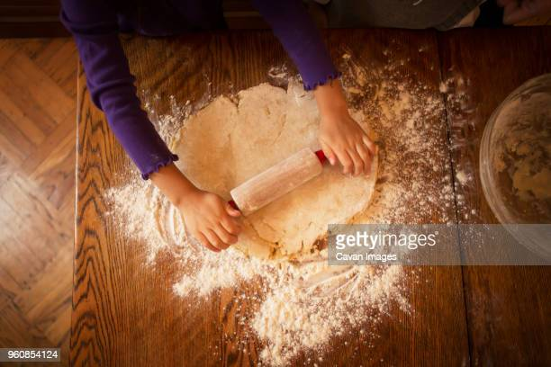 Cropped image of hands rolling pastry dough for preparing cookies during Christmas