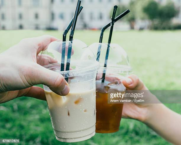 Cropped Image Of Hands Toasting Iced Coffee In Disposable Cups At Park