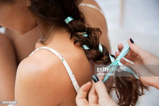 cropped image of hands tying womans hair while sitting in tent - weaving stock pictures, royalty-free photos & images