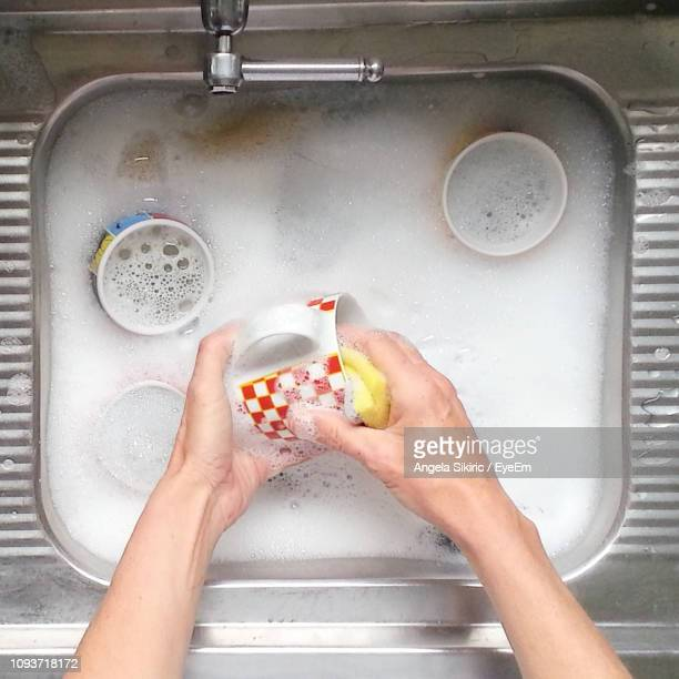 cropped image of hands washing cups in sink - washing up stock pictures, royalty-free photos & images