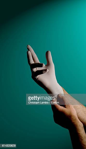Cropped Image Of Hands Wearing Surgical Glove Against Turquoise Wall