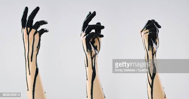 Cropped Image Of Hands With Black Paint Against White Background