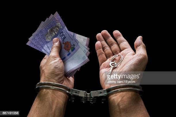 Cropped Image Of Hands With Handcuffs Holding Paper Currencies Against Black Background